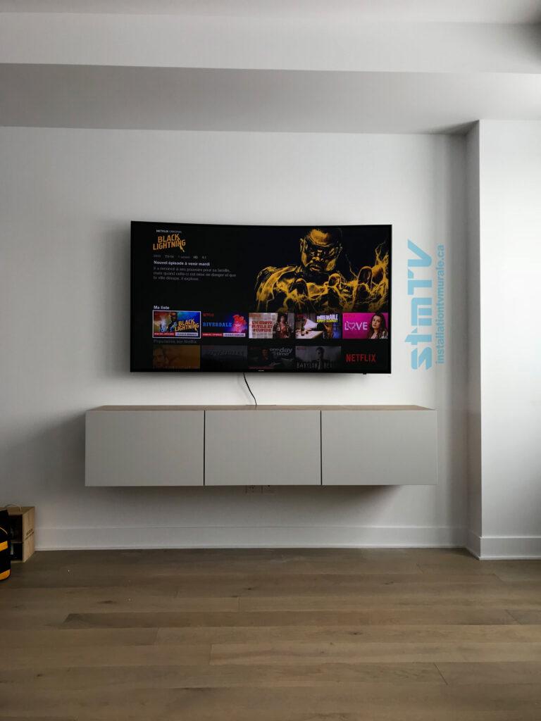 Installation d'une tv au mur avec support murale. Console media murale également fixé au mur.